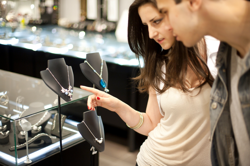 Attractive young couple looking at fine jewelry at a boutique