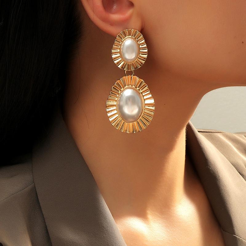 a woman wearring big pearl earrings