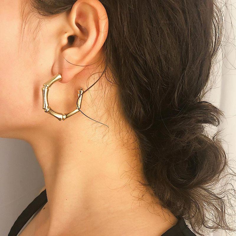 a women wearring bamboo alloy earrings