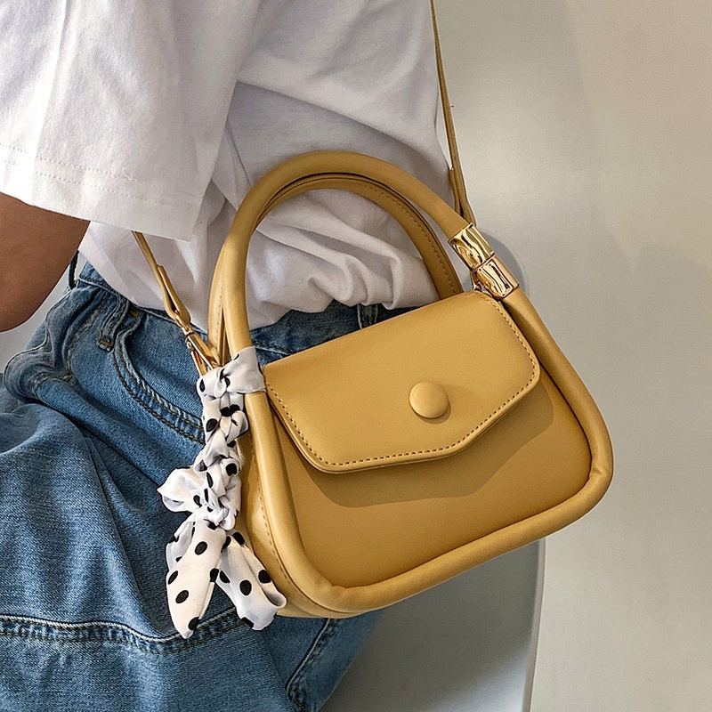 a yellow bag with silk satin scarf on it
